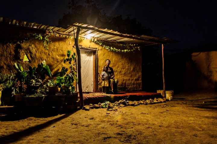 A woman and her daughter sit on their porch lit by a solar micro-grid in Ngwerere, Zambia